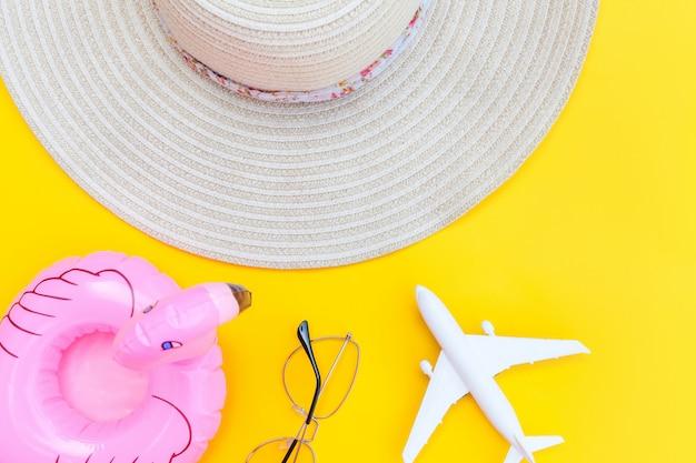 夏のビーチの組成物。飛行機のサングラスの帽子と黄色に分離されたインフレータブルフラミンゴの最小限のシンプルなフラットレイアウト。休暇旅行冒険旅行のコンセプトです。トップビューコピースペース。
