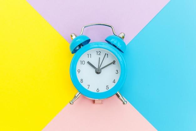 リンギングツインベルクラシックな目覚まし時計は、ブルーイエローピンクパステルカラフルな幾何学的に分離されました。おやすみなさいおやすみなさいおやすみなさいフラット横たわっていたトップビューコピースペース。