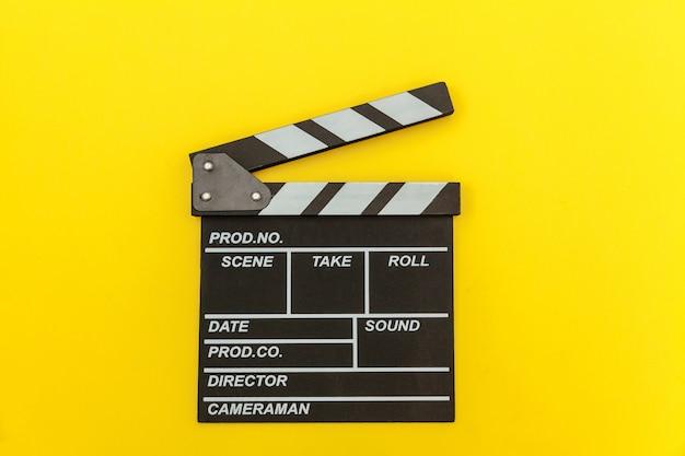 Кинопроизводитель по профессии. классический режиссер пустой фильм делает с 'хлопушкой' или фильм шифер, изолированные на желтом фоне. видео производство фильмов киноиндустрия концепции. плоские лежал вид сверху копией пространства макет.