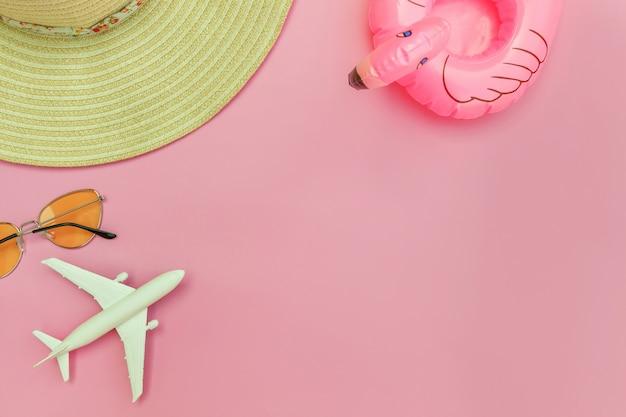 夏のビーチの組成物。飛行機のサングラスの帽子とパステルピンクの背景に分離されたインフレータブルフラミンゴと最小限のシンプルなフラットが横たわっていた。休暇旅行冒険旅行のコンセプトです。トップビューコピースペース。