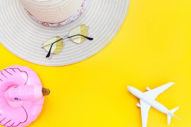 夏のビーチの組成物。飛行機のサングラスの帽子と黄色の背景に分離されたインフレータブルフラミンゴと最小限のシンプルなフラットが横たわっていた。休暇旅行冒険旅行のコンセプトです。トップビューコピースペース。