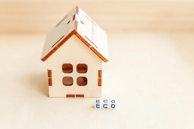 Миниатюрная игрушка модель дома с надписью эко буквы слова на деревянной поверхности. эко вилидж. экология безотходная социальная ответственность переработка концепции био дома