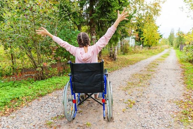 自由を楽しんでいる病院の公園の道路上の車椅子の若い幸せなハンディキャップの女性。自然の中で屋外の障害者のための無効な椅子で麻痺した少女。リハビリテーションの概念。