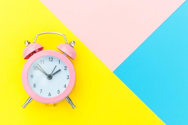 青黄色ピンクパステルカラフルな幾何学的な背景に分離されたツインベル古典的な目覚まし時計を鳴っています。おやすみなさいおやすみなさいおやすみなさいフラット横たわっていたトップビューコピースペース。