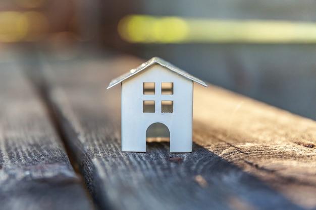 木製の背景のミニチュアの白いおもちゃモデルハウス。エコビレッジ、抽象的な環境背景