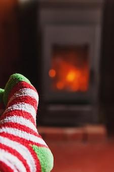 Ноги в зимних шерстяных носках у камина