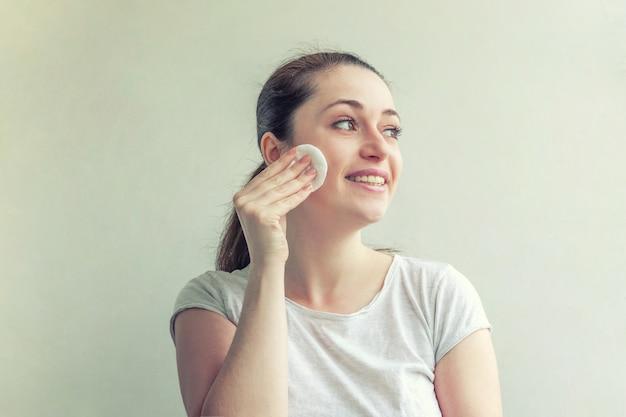 白い壁に分離された綿のパッドでメイクアップを柔らかく健康的な皮膚を取り除くと笑顔の女性