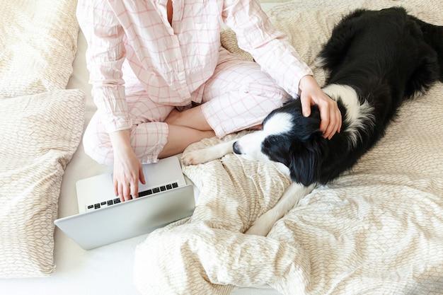 Мобильный офис дома. молодая женщина в пижамах сидя на кровати при использование собаки любимчика работая на компьютере пк компьтер-книжки дома. образ жизни девушка учится в помещении. концепция карантинного бизнеса фриланс.