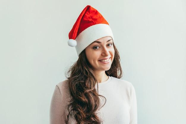 Красивая девушка в красной изолированной шляпе санта-клауса