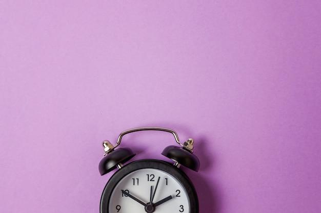 Старинный будильник изолирован на фиолетовом