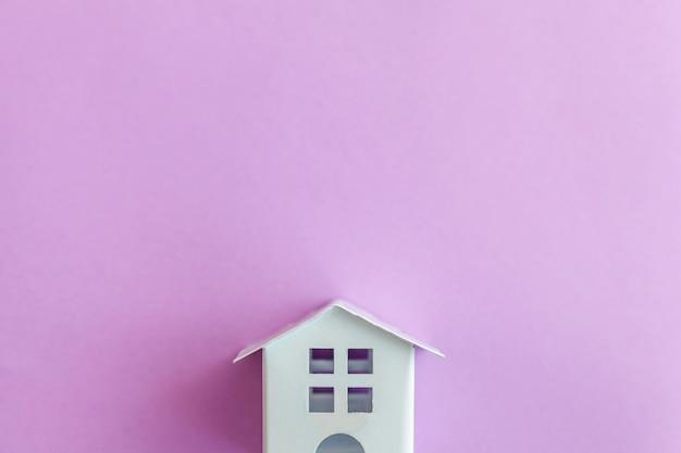 Миниатюрный белый игрушечный домик на фиолетово-фиолетовом фоне пастельных