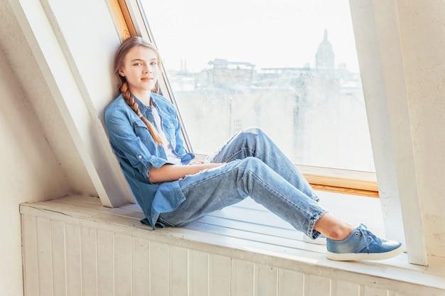 Оставайтесь дома, оставайтесь в безопасности. молодая милая девушка в джинсах, джинсовой куртке и белой футболке, сидя на подоконнике в ярком свете гостиной дома в помещении и мышления. концепция социальной дистанции джомо.