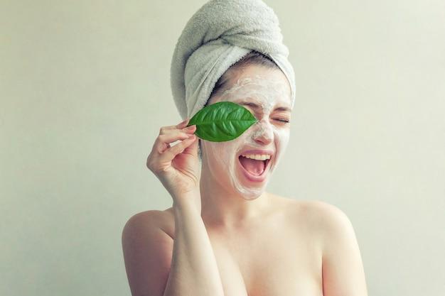 緑の葉とクリームまたは栄養マスクを持つ女性の顔