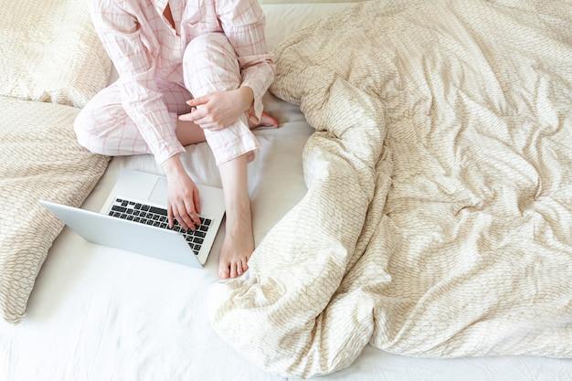 Молодая женщина в пижаме, сидя на кровати у себя дома работает с использованием портативного компьютера
