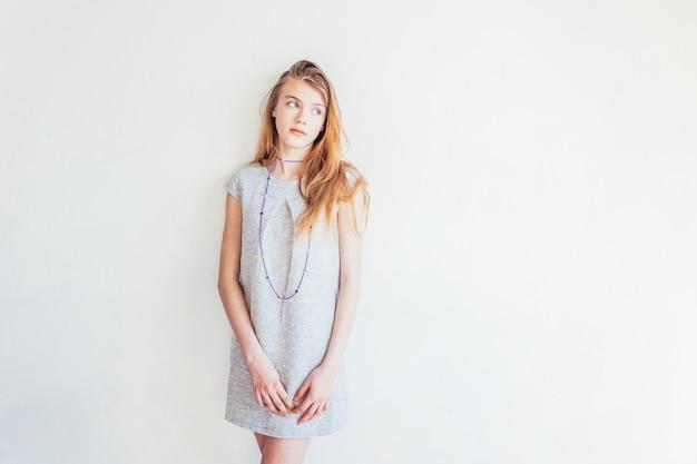 白い壁の背景に灰色のドレスの肖像若い十代の少女