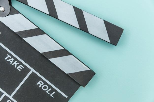 青の背景に分離されたカチンコや映画スレートを作る監督空の映画