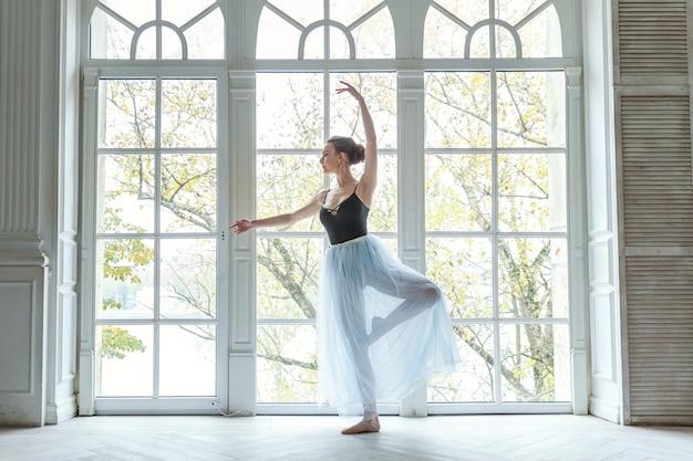 若い古典的なバレエダンサーの女性が白い光ホールの大きな窓の近くのダンスクラスでバレエの位置を練習します。