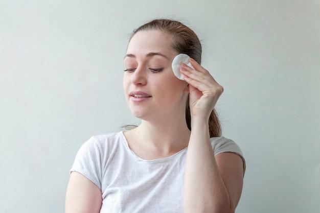 白い壁に分離された綿のパッドとメイクアップを取り除く柔らかな健康的な肌を持つ女性