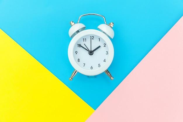 Звонит двойной звонок классический будильник, изолированный на синем желто-розовом пастельно-красочном геометрическом фоне