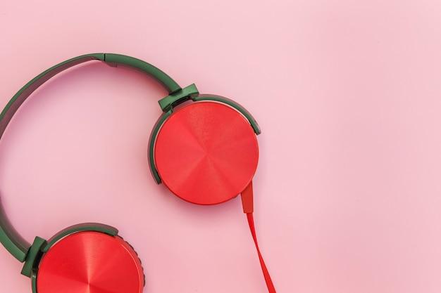 ピンクのパステル調のカラフルな背景に分離されたケーブルと赤いヘッドフォン
