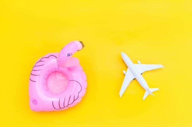 飛行機と黄色の背景に分離されたインフレータブルフラミンゴの最小限のシンプルなフラットレイアウト