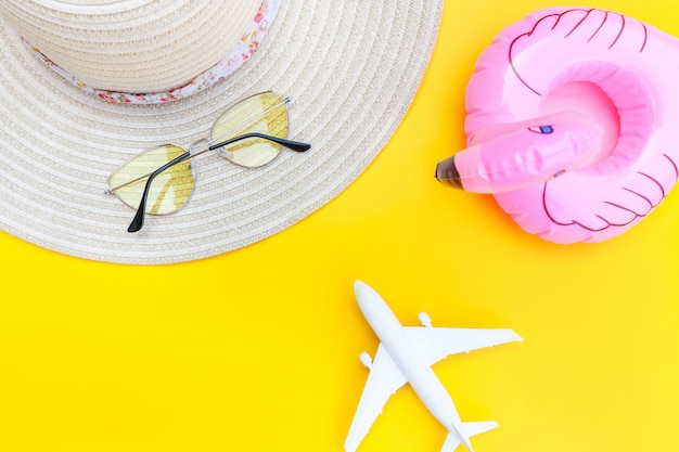 飛行機のサングラスの帽子と黄色の背景に分離されたインフレータブルフラミンゴの最小限のシンプルなフラットレイアウト