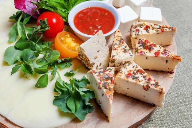 Доска с разными видами сыра фета-брынза, томатным соусом и свежими овощами. ресторанное меню