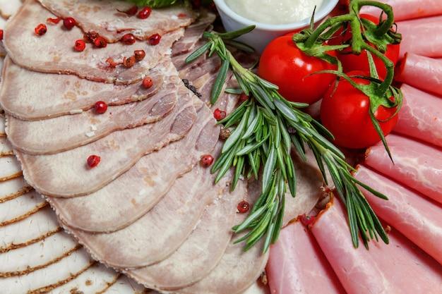 さまざまな種類の肉とハムの珍味、ソース、新鮮な野菜のボード。レストランメニュー盛り合わせ