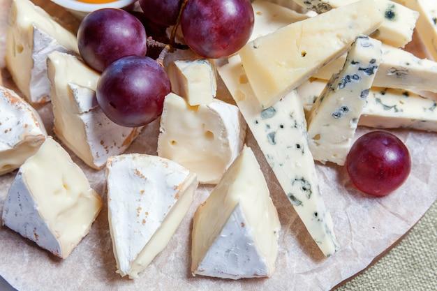 Доска с разными видами сыра: дорблю, чедер, пармезан, бри, медовый соус, хлеб из пальчиков и виноград. ресторанное меню
