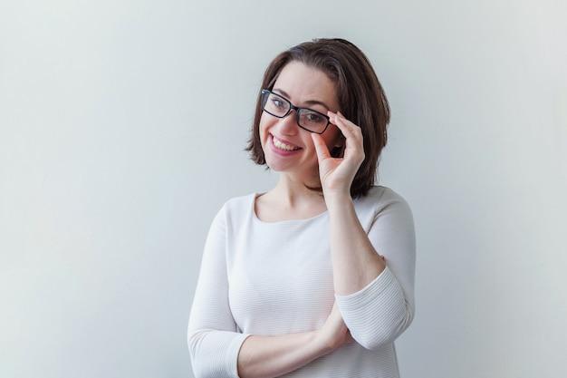 笑っている美しい幸せな女の子。白で隔離の眼鏡の美しさシンプルな肖像若い笑顔ブルネットの女性