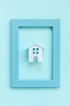 カラフルなパステルブルーに分離された青いフレームのミニチュア白いおもちゃの家で単に設計