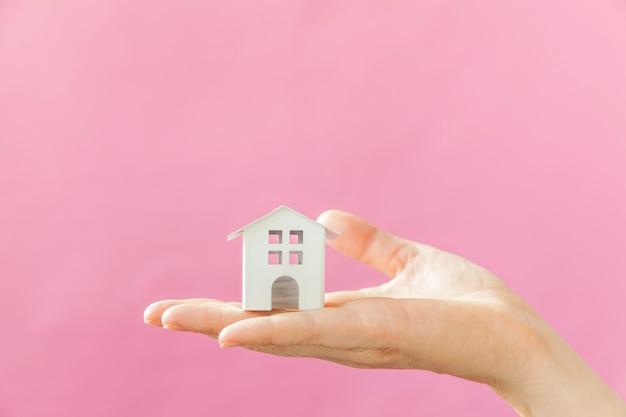 ピンクのパステルカラーのカラフルなトレンディに分離されたミニチュアの白いおもちゃの家を持つ女性の女性の手を単に設計します。
