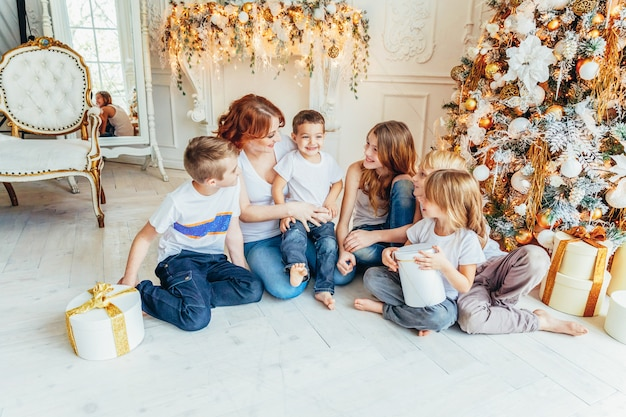Счастливая семья мать и пятеро детей отдыхают, играя возле елки в канун рождества у себя дома. мама дочки сыновья в светлой комнате с зимним украшением. рождество новый год время для празднования