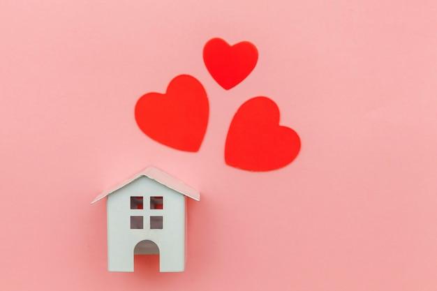 ピンクのパステルカラーのカラフルなトレンディに分離された赤いハートとミニチュアの白いおもちゃの家でシンプルなデザイン