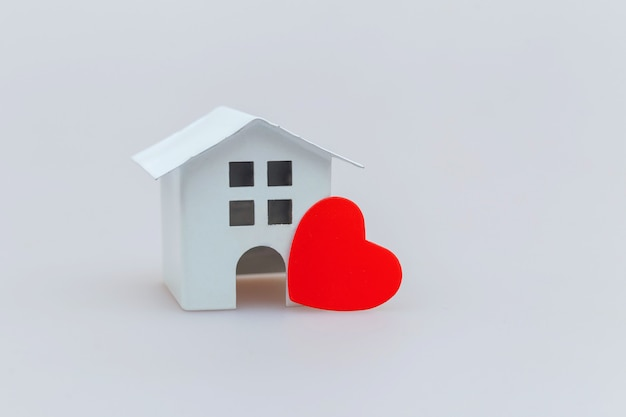Просто минималистичный дизайн с миниатюрным белым игрушечным домиком с красным сердцем на белом