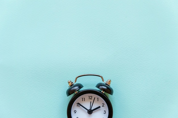青いパステル調の背景に分離されたビンテージの目覚まし時計