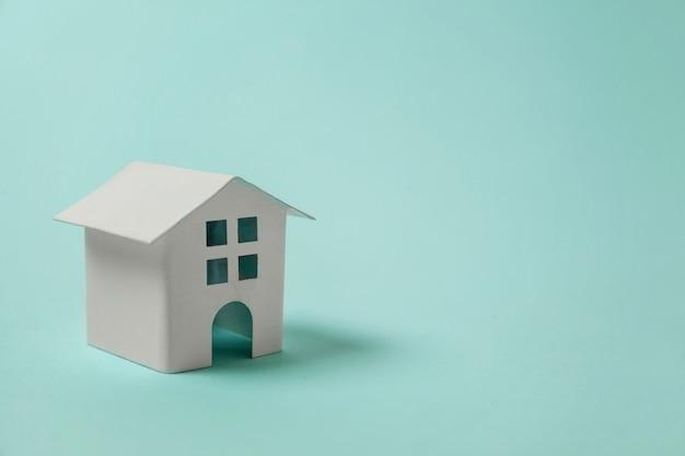 青色の背景にミニチュアの白いおもちゃの家