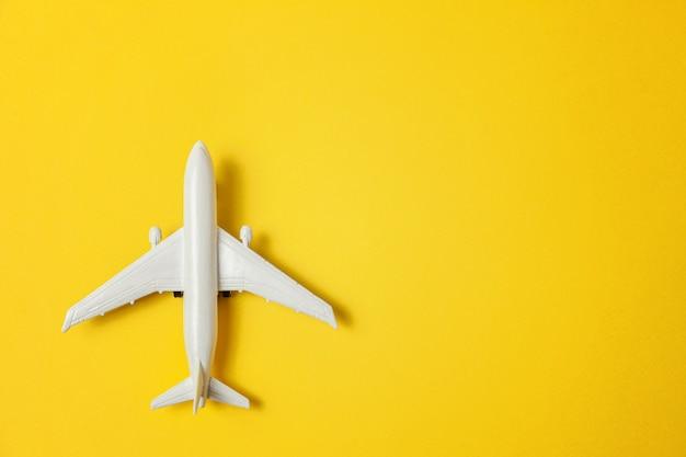 カラフルな黄色の背景におもちゃの飛行機