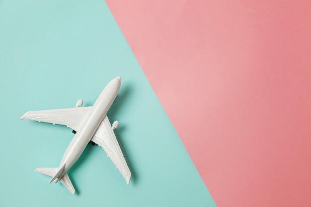 カラフルなピンクと青の背景におもちゃの飛行機