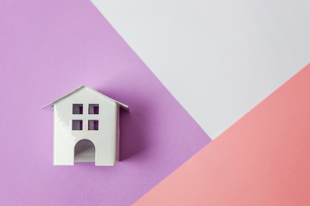 Миниатюрный белый игрушечный домик на белом фиолетово-розовом пастельном фоне