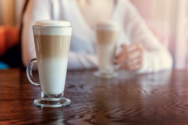 背の高いグラスにラテマキアートドリンクをクローズアップ。カフェのテーブルの上のコーヒー生クリームカプチーノ。