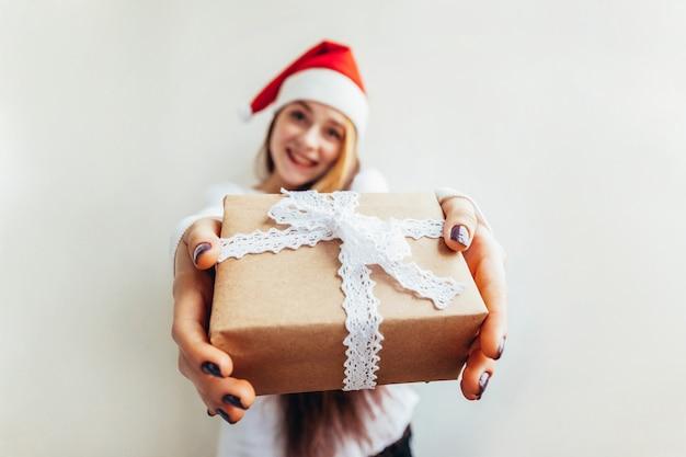Красивая девушка с длинными волосами в красной шляпе санта-клауса, холдинг подарочной коробке, изолированные на белом, глядя счастливы и рады.
