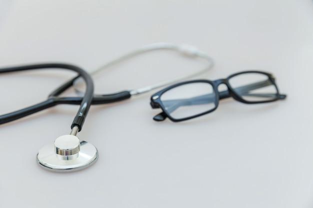 Медицинское оборудование стетоскоп или фонендоскоп и очки изолированы. приборное устройство для врача. медицинское страхование жизни