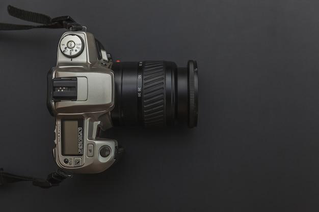 暗い黒いテーブルにデジタル一眼レフカメラシステムと写真家の職場。趣味旅行写真コンセプト