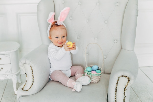 Маленькая девочка ребенка носить уши кролика в день пасхи и играть с крашеными яйцами