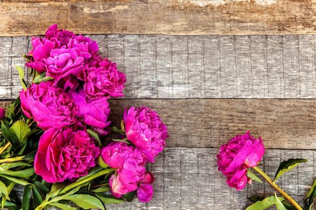 Цветочная рамка с розовыми пионами на деревянном фоне