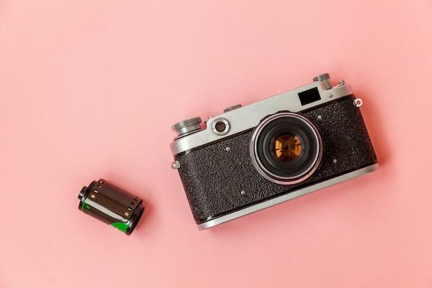 技術開発の流行に敏感な写真家趣味の古典的なメモリ旅行のコンセプト。ピンクのパステル調のトレンディな現代ファッションピンナップ背景にビンテージフィルム写真カメラレンズとフィルムロール