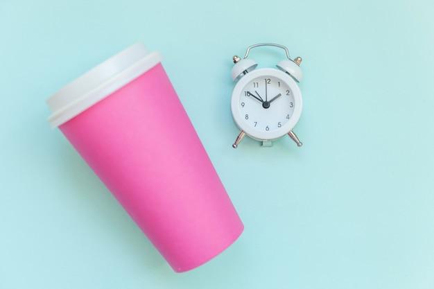Просто плоская планировка розовой бумаги кофейная чашка и будильник, изолированных на синем фоне пастельных красочных