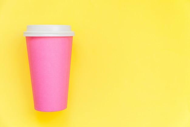Просто плоский дизайн лежал розовой бумаге кофейной чашки, изолированных на желтом красочном модном фоне