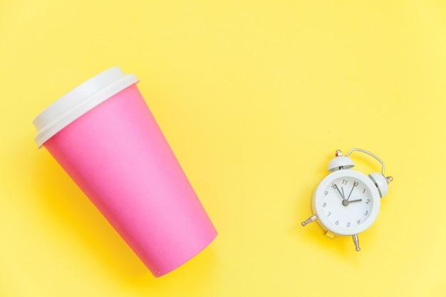 Просто плоская планировка розовой бумаги кофейная чашка и будильник, изолированных на желтом красочном модном фоне